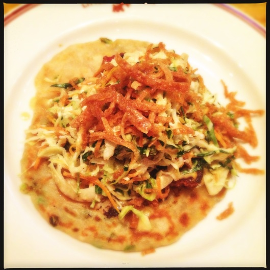 A scallion pancake topped with pork-belly and bok-choy at The Little Goat